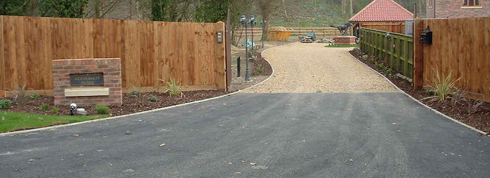 Asphalt drive entrance with kerbstone edging and shingle drive, fencing, turf, garden lighting and landscaping